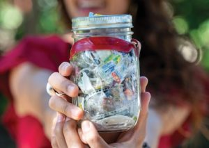 Girl holding a Mason jar filled with 1-year of trash