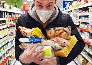 Shopper with a mask and gloves hoarding food in a supermarket.