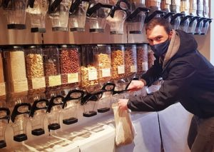 Guy filling up organic pasta in a bulk shop.