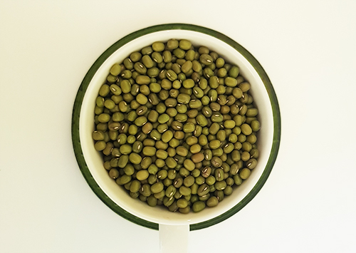 Cup of dried mung beans viewed from top.