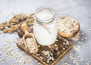 Jar of oat milk with oat flakes.