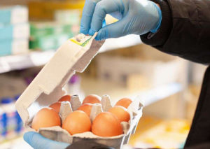 Shopper opening an egg box with plastic gloves.