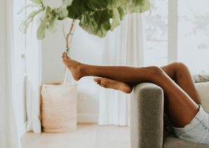 Girl's leg relaxing on a couch in a blogger appartment.