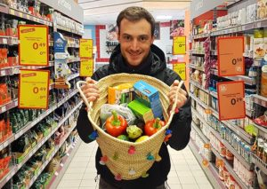 Man carrying a tote bag full of sustainable groceries in a supermarket.