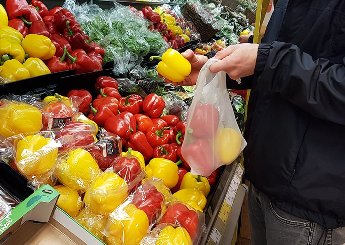 Customer in a supermarket stuffing paprika in a reusable bag.