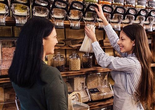 Bulk shop owner filling in food in a jar.