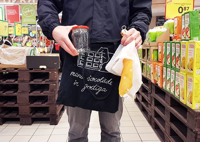 Man holding a tote bag, fabric bags, and a glass jar in a supermarket.