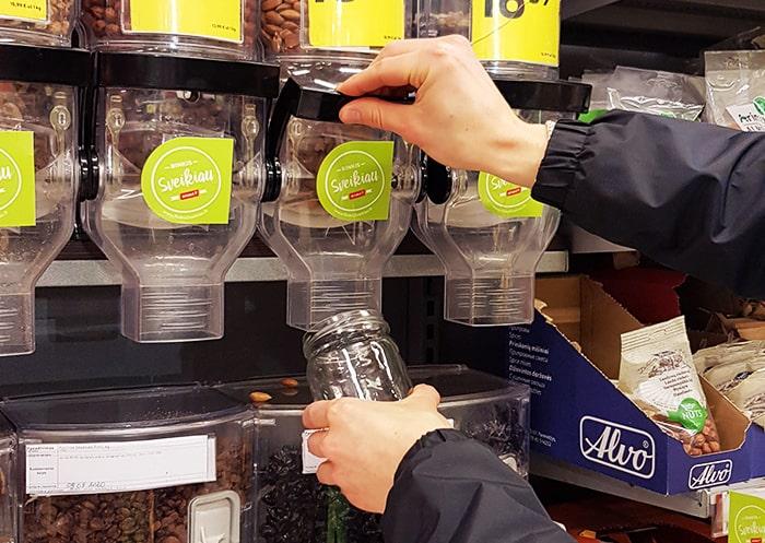 Man serving nuts from a bulk dispenser in a glass jar.