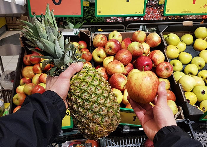 Hands holding a pineapple and a local apple.