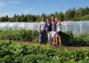Heartmade family standing in front of the greenhouse of the eco-farm.