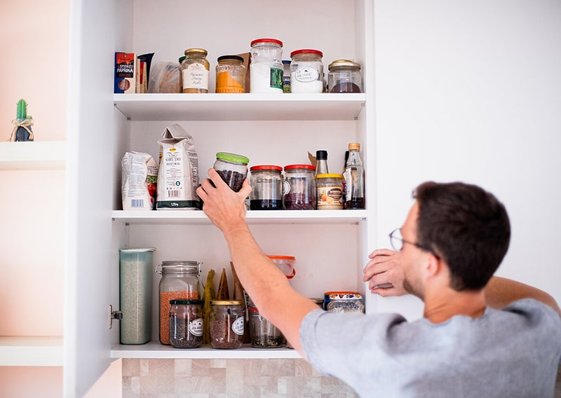 Man reaches for glass jar in pantry