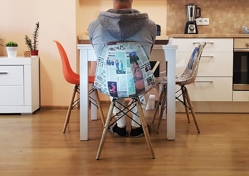 Man sitting on a chair refurbished with recycled newspaper.