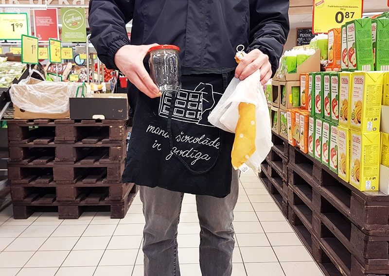 Man holding glass jar and cloth bags in grocery store