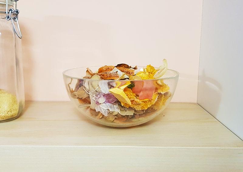 glass bowl with organic food waste on shelf