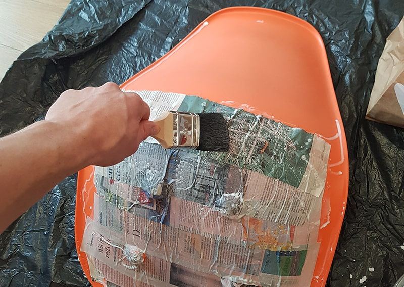 Men brushing the newspaper strip on the chair.